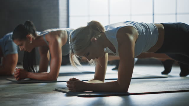 strong masculine man and two fit atletic women hold a plank position in order to exercise their core strength. blond girl is exhausted and fails the training first. they workout in a loft gym. - fare la lotta video stock e b–roll