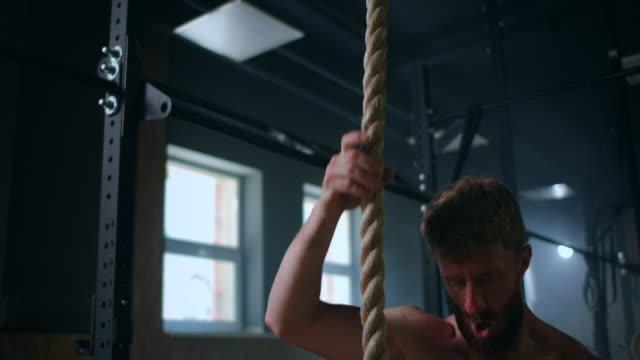 uomini forti durante l'allenamento salire la corda verso l'alto. formazione per i soccorritori. esercizio fisico per la resistenza e la coordinazione. - inerpicarsi video stock e b–roll