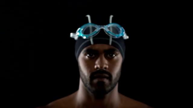 nuotatore forte e motivato che si mette gli occhiali, si prepara alla competizione - occhiali protettivi video stock e b–roll