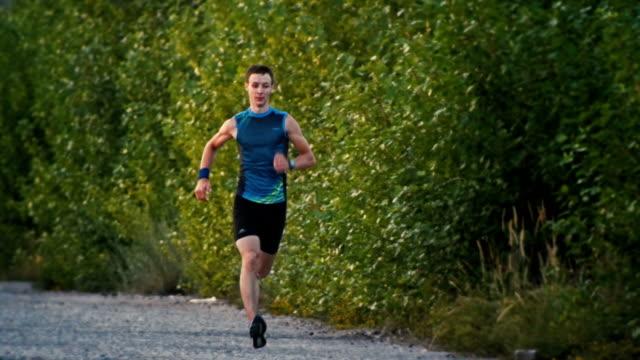 stark muskel löpare man kör i park i skymning, slow motion, bred vinkel - tävlingsdistans bildbanksvideor och videomaterial från bakom kulisserna