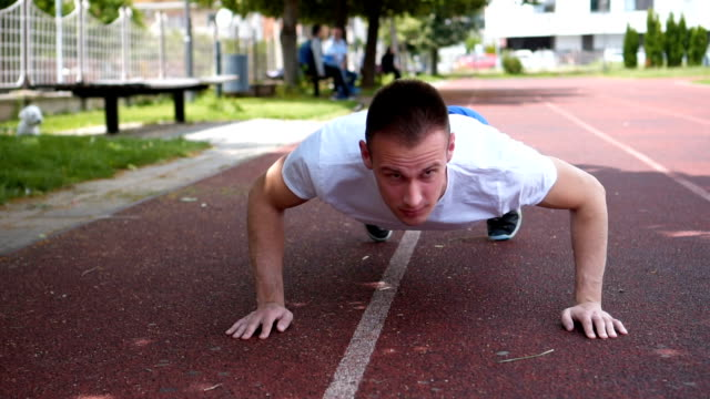 Strong Muscular Fit Young Man Exercise push-ups on the field Strong Muscular Fit Young Man Exercise push-ups on the field bodyweight training stock videos & royalty-free footage