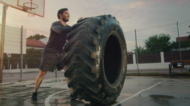 Strong Muscular Fit Young Man in Sport Outfit and Gloves is Doing Exercises in a Fenced Outdoor Basketball Court. He's Flipping a Big Heavy Tire in an Afternoon Environment After Rain. Strong Muscular Fit Young Man in Sport Outfit and Gloves is Doing Exercises in a Fenced Outdoor Basketball Court. He's Flipping a Big Heavy Tire in an Afternoon Environment After Rain. Shot on RED EPIC-W 8K Helium Cinema Camera. cross training stock videos & royalty-free footage