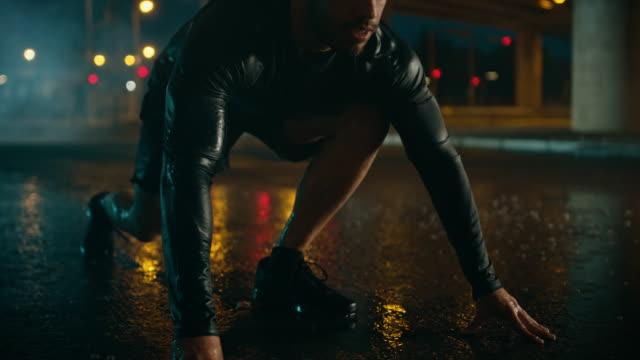 güçlü kas uygun genç adam yağmurlu bir akşam sprint başlar. bridge'de bir kentsel çevre altında bir otomobil içinde belgili tanımlık geçmiş ile çalışıyor. - başlama çizgisi stok videoları ve detay görüntü çekimi