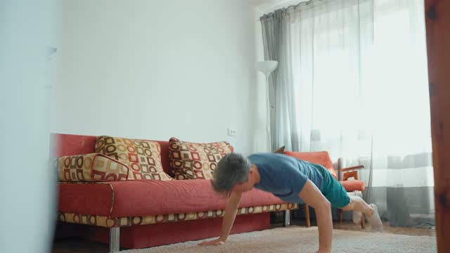strong muscular man in sportswear doing exercises at home