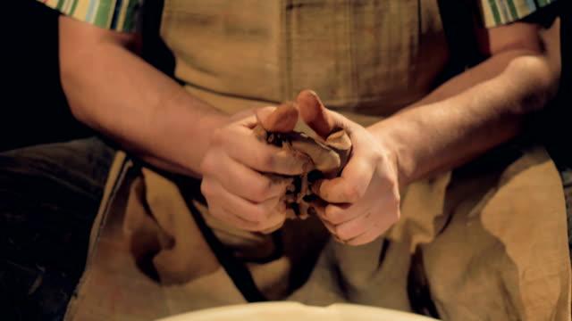 vídeos de stock, filmes e b-roll de fortes mãos ceramistas amasse um pedaço de barro. - domínio