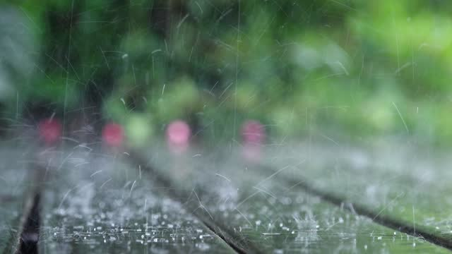 Strong rain drops falling on outdoor wooden deck