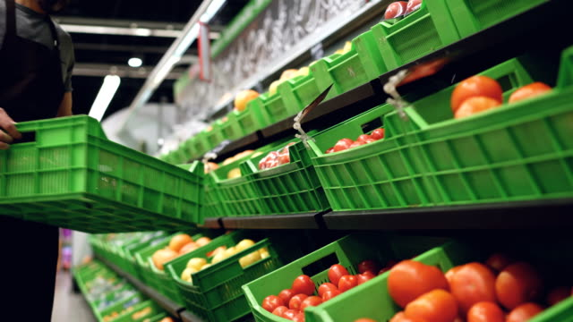 vídeos de stock e filmes b-roll de strong salesman wearing uniform is bringing plastic box of tomatoes and putting on shelf in supermarket in fruit and vegetables department. containers with food are visible. - supermarket worker