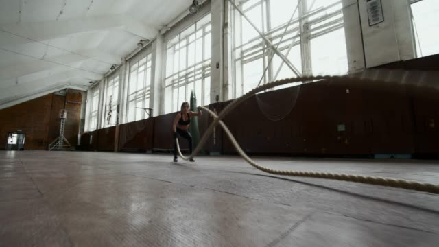 Strong Sportswoman Balling Ropes PAN of strong fit sportswoman battling ropes during conditioning workout routine in empty gymnasium cross training stock videos & royalty-free footage
