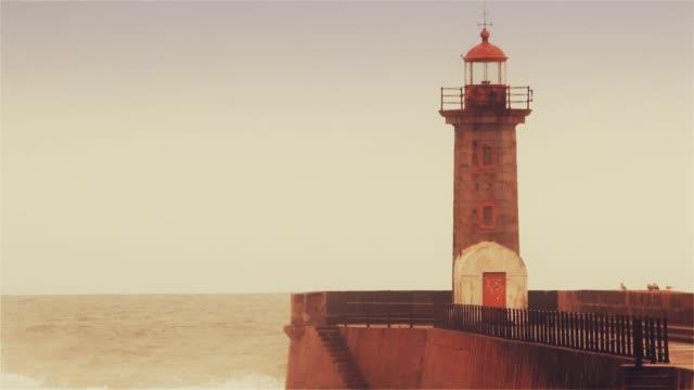vídeos de stock e filmes b-roll de strong waves break about the pier, the lighthouse on the shore of the atlantic ocean - rain clouds porto portugal