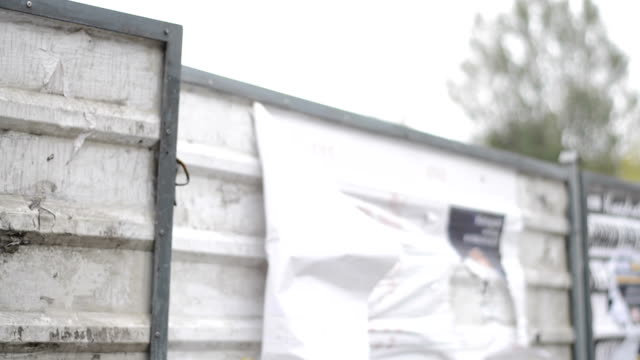 Strong wind, fence, torn posters video