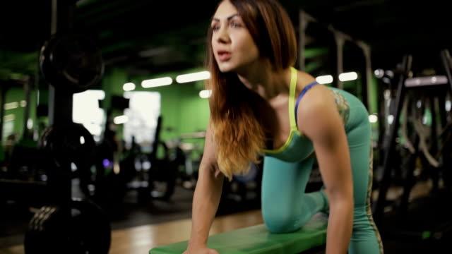 vídeos de stock, filmes e b-roll de mulher forte que faz o exercício na ginástica. ela está levantando o dumbbell. - comodidades para lazer