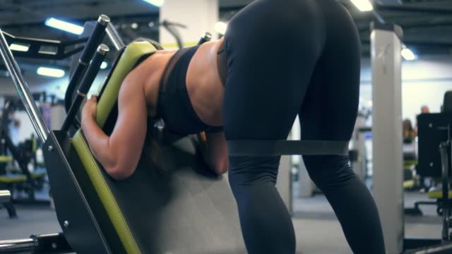 vídeos de stock e filmes b-roll de strong woman exercising on reverse squat machine - agachar se
