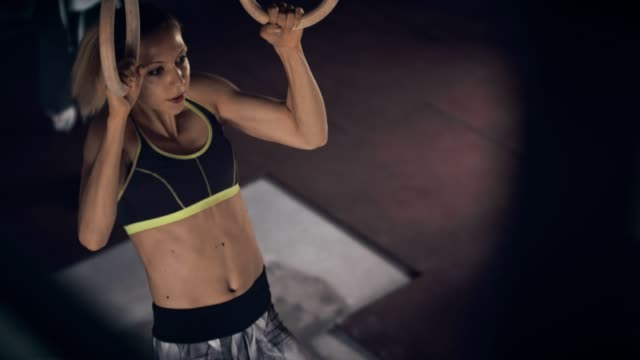 strong woman on gym rings - donna forzuta video stock e b–roll