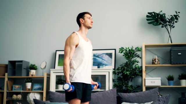 집에서 팔과 어깨를 작동 덤 벨과 강한 젊은 남자 훈련 - 웨이트 스톡 비디오 및 b-롤 화면