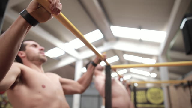 machthaber tun klimmzüge auf gymnastik balken im fitness-studio - turngerät mit holm stock-videos und b-roll-filmmaterial