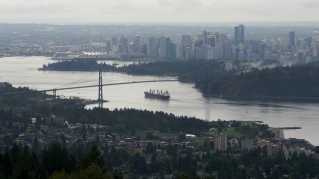 Structure of Lions Gate Bridge, cargo ship moving in sea, Vancouver, British Columbia, Canada. - video