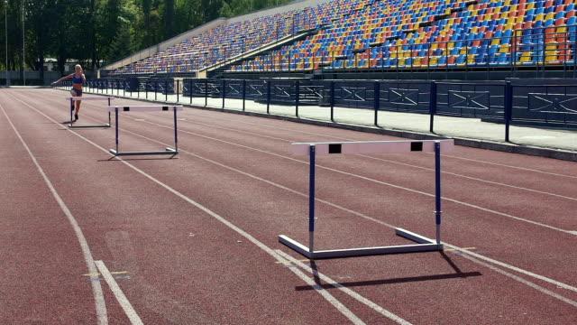 vídeos y material grabado en eventos de stock de terca niña pasar días en el estadio, entrenamiento antes de la competencia de carrera de obstáculo - valla artículos deportivos