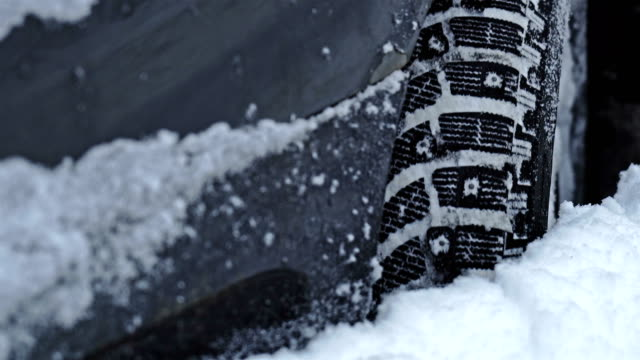 Studded car tire turns and slips in the deep snow close up video