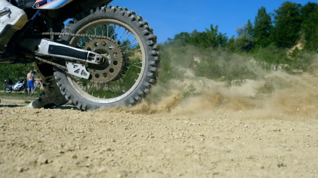 Studded motocross wheel starting to spin and kicking up ground or dirt. Motorcycle starts the movement. Slow motion Close up Side view Low angle view