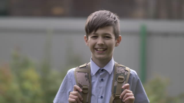 student boy with a backpack looks at the camera and laughs outdoors - solo un bambino maschio video stock e b–roll