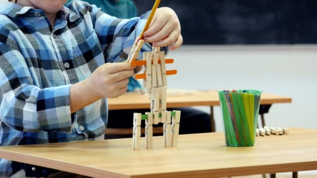 Student concentrates while building something in after school engineering club builds something with popsicle sticks and clothes pins. He is in an after school engineering club. A teacher and student are in the background. Handheld camera pans from the bo video