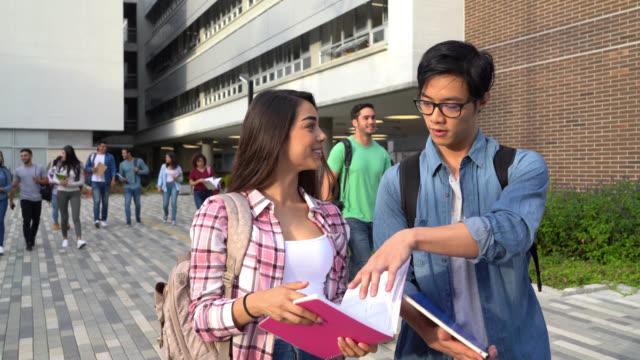 vídeos de stock, filmes e b-roll de pares do estudante que andam afastado do terreno após a classe que verific algumas notas que falam e que sorriem - gênero humano