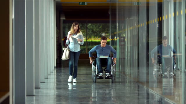 SLO MO DS Student Diversity HD1080p: SLOW MOTION LONG DOLLY shot of a young female student having conversation with her classmate in a wheelchair while walking down the corridor of the college. wheelchair stock videos & royalty-free footage