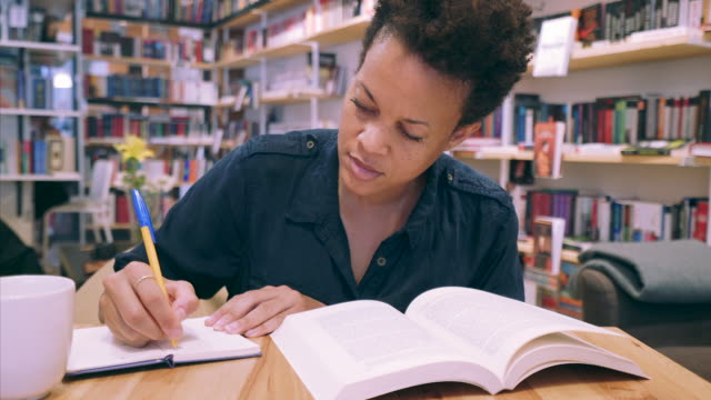stockvideo's en b-roll-footage met student huiswerk in bibliotheek. - boekenkast