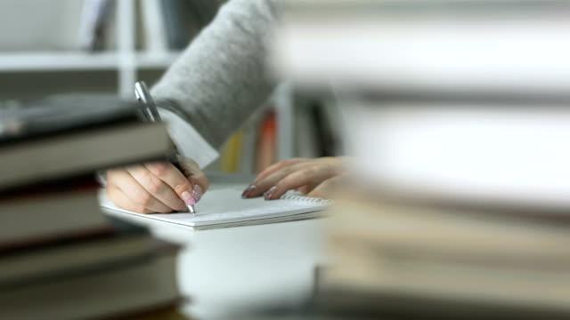 hd: studente facendo i compiti in biblioteca - rack focus video stock e b–roll