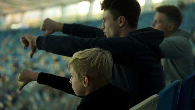 Student fans and little boy booing sport game at stadium, watching junior match