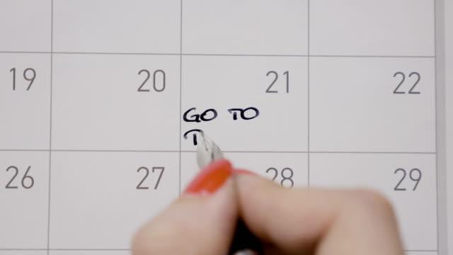 student kvinnliga händer skriver med svart penna kalendern gå till pilates med versaler - calendar workout bildbanksvideor och videomaterial från bakom kulisserna