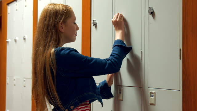 Student gathering her school books from a locker Student gathering her school books from a locker in the university college locker stock videos & royalty-free footage