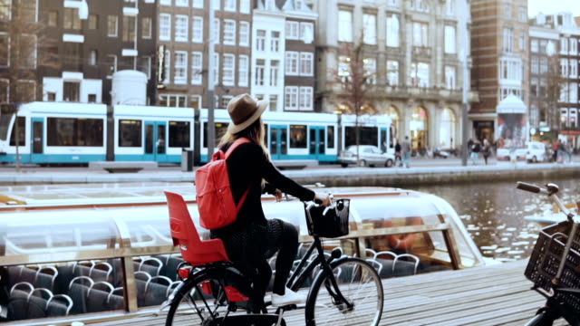 student girl cycling bicycle along a river quay. local commuter. female in hat cruising on a city bike. slow motion - amsterdam video stock e b–roll