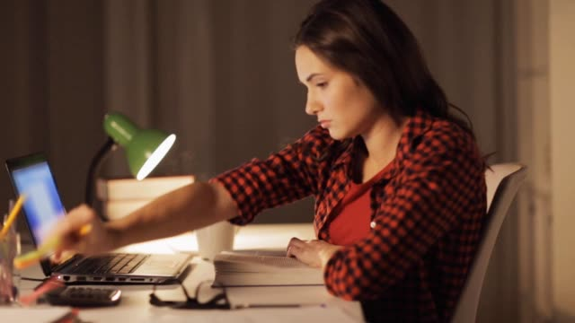 student girl or woman reading book at night home