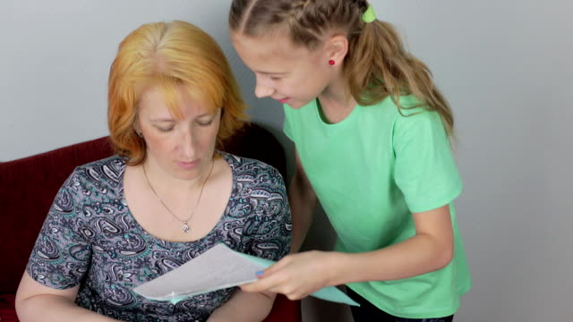 Student girl shows her mother a good grade video