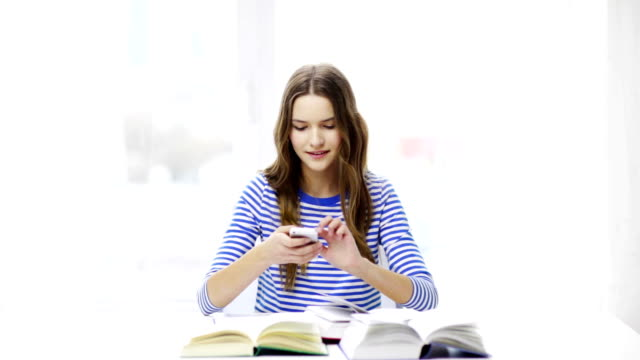 student girl with smartphone and books learning at home - esame maturità video stock e b–roll