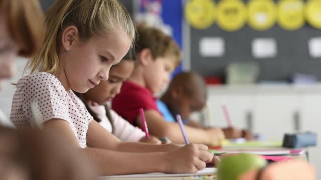 studentin am lehrbuch schreiben - grundschule stock-videos und b-roll-filmmaterial