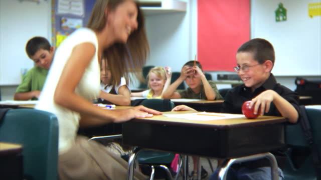 teilnehmer gibt lehrer einen apple - grundschule stock-videos und b-roll-filmmaterial