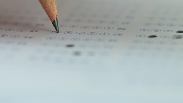 大学の期末試験における解答用紙の選択された選択肢を鉛筆画で試験している学生の手のテスト。試験教室での評価のための複数の選択肢を取る ビデオ