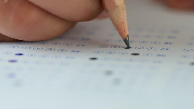 test a mano degli studenti facendo esame di prova con disegni a matita scelte selezionate sul foglio di risposte negli esami finali scolastici al college o all'università. scelta multipla per la valutazione in aula d'esame - esame università video stock e b–roll