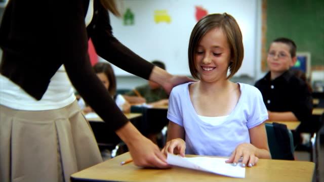student hält ein papier mit einem - grundschule stock-videos und b-roll-filmmaterial