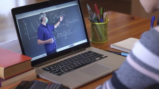 stockvideo's en b-roll-footage met student leren door middel van educatieve video-oproep met wiskunde leraar die het dragen van gezichtsmasker. online les vanwege coronavirus pandemie - online leren