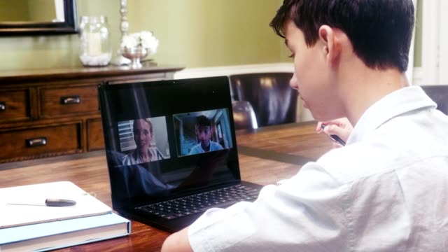 Student learns from home during COVID-19 crisis A mixed race middle school student talks with his teacher via video call while distance learning during the COVID-19 crisis. middle school teacher stock videos & royalty-free footage