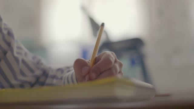 vídeos y material grabado en eventos de stock de estudiante masculino mano escribe cuaderno en blanco educación concepto - clase de matemática