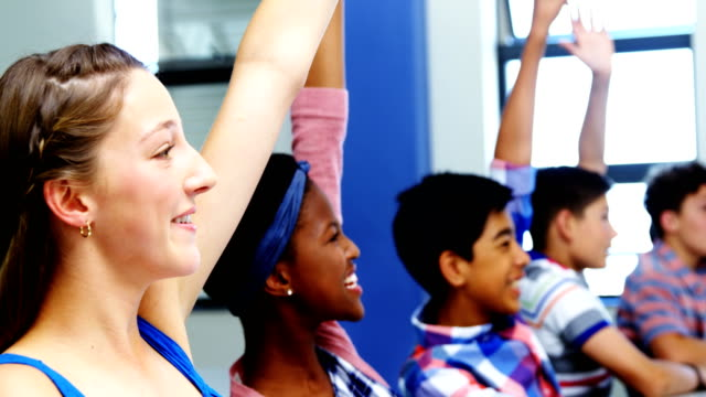 Student raising hand in classroom video