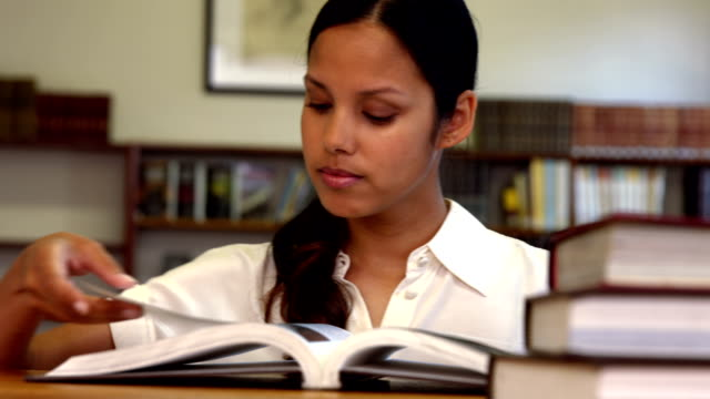 Student reading a book from shelf in library video