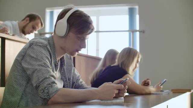 A student sitting in a university auditorium with a large group of people sits in headphones and listens to music and looks at the smartphone screen. It is in a state of calm. Class break.