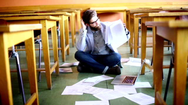 Student struggling with papers. video