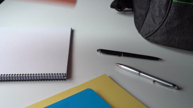 Student teenager collects a gray bag on a white table for school Student teenager collects a gray bag on a white table for school. Notebooks, pens, textbooks, pencil case, school bag school supplies stock videos & royalty-free footage