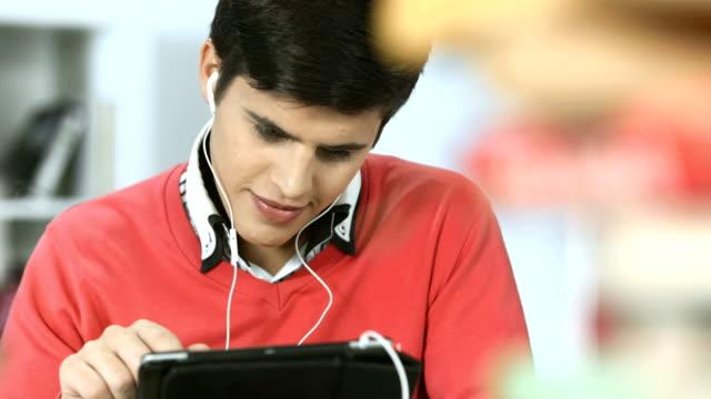 hd: student using digital tablet in the library - kulaklık seti ses ekipmanı stok videoları ve detay görüntü çekimi